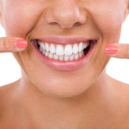 Frau lächelt und zeigt auf ihre Zähne