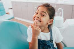 Kind zeigt Zähne beim Zahnarzt